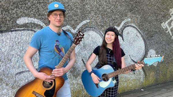 Reporter Robert fasst all seinen Mut zusammen und macht das erste Mal Straßenmusik. Musikerin Sarah Hübers unterstützt ihn dabei.   Rechte: WDR/tvision