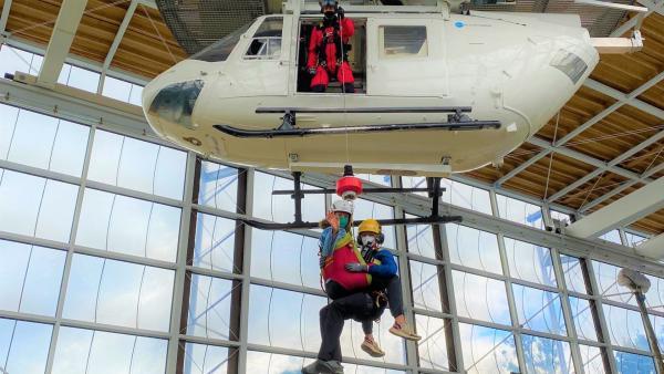 Bei einer Übung wird Reporterin Gesa (links) wird von Bergretterin Kristina aus einer Gondel gerettet. | Rechte: WDR/tvision