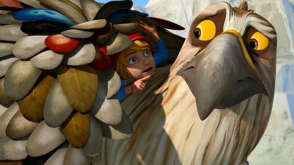 Um Gorgo Tips zu geben, wie man sich als Adler verhält, versteckt Nils sich unter angesteckten Federn auf Gorgos Rücken. | Rechte: BR/Studio 100 Animation/Studio 100 NV
