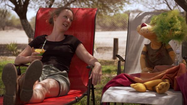 OLI und Davina sitzen gemütlich im Garten ihrer Farm in Afrika. Da klingelt das Telefon. Die beiden sollen einen Leoparden auswildern. | Rechte: SWR