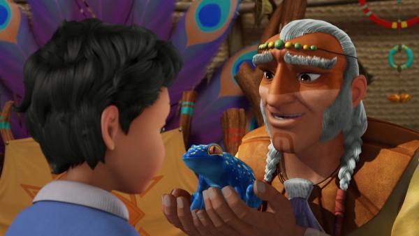 Der Häuptling übergibt den Frosch Pakwa an Michael. Michael darf auf den kleinen Hüpfer aufpassen, während der Häuptling mit seinem Stamm nach magischen Pflanzen sucht. | Rechte: ZDF/DQ Entertainment