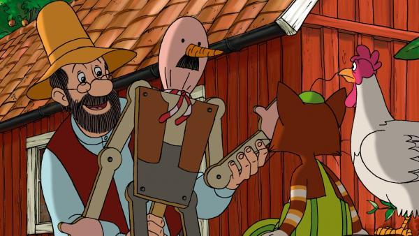 Pettersson (li.) zeigt Findus (re.) seine selbst gebaute Vogelscheuche, um die Kraniche zu vertreiben. | Rechte: ZDF/TV Loonland