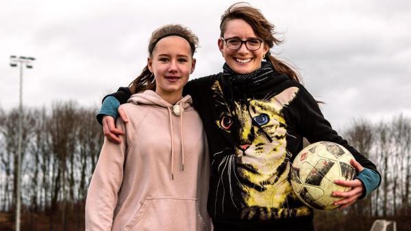 Die Princess of Science Johanna (re.) steht neben einer Sportlerin (li.) in der Sporthalle. In den Händen halten sie Stäbe für den Stabhochsprung. | Rechte: ZDF/ Martin Vogel