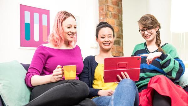 Die drei Wissenschaftlerinnen Johanna, Linh und Patrizia sitzen in ihrem Co-Working-Space auf einem Sofa und schauen gemeinsam in ein Tablet mit pinker Hülle.   Rechte: ZDF/ Martin Vogel