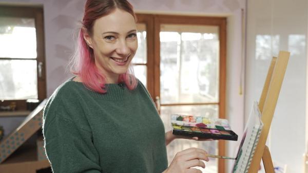 Princess Johanna (li.) mal mit Farbe auf eine Leinwand, die auf einer Staffelei (re.) steht. In einer Hand hält sie einen Tuschkasten mit Wasserfarben. | Rechte: ZDF/ Martin Vogel