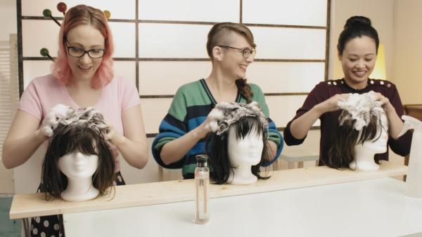 Johanna (li.), Patrizia (mi.) und Linh (re.) shamponieren die Haare der vor sich stehenden Puppenköpfe. | Rechte: ZDF / Martin Vogel
