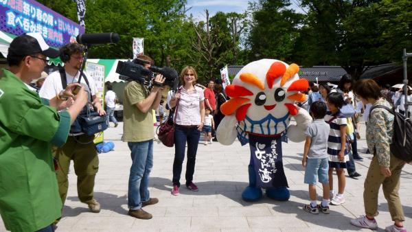 Moderator Eric Mayer als Maskottchen mit Team in Tokyo. | Rechte: ZDF/Ulrike Schenk