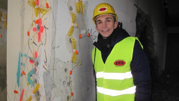 pur+-Moderator Eric Mayer vor einer mit Sprengsätzen präparierten Wand. | Rechte: ZDF/Carina Schulz