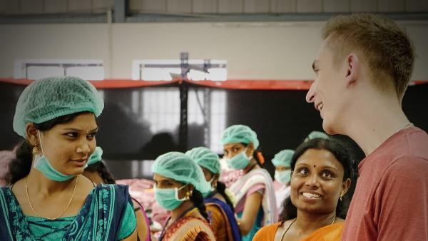 Wie lange arbeitet ihr täglich? Und wie viel verdient ihr? Eric fragt bei Arbeiterinnen in einer südindischen Näherei nach. | Rechte: ZDF/Zeljko Pehar