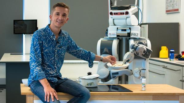 """Ein Roboter macht Popcorn!? """"PUR+""""-Moderator Eric Mayer lernt """"PR2"""" kennen, der an der Universität Bremen mithilfe von Künstlicher Intelligenz Küchenarbeiten erlernt. Schafft er es auch, einen Tisch zu decken? Kann er sich die unterschiedlichen Gegenstände dafür selbst zusammensuchen?   Rechte: ZDF/Pablo Wolff"""