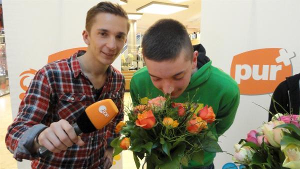 Eric Mayer, pur+ Stuntman des Wissens beim Geruchstest. Passanten sollen am Geruch feststellen, welchen Blumenstrauß, die vorher mit einem Duft eingesprüht wurden, sie eher kaufen würden. | Rechte: ZDF/Sandra Palm