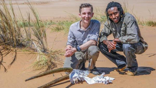 Eric kniet mit Titus in der Wüste hinter dem Schädel eines Tiers. | Rechte: ZDF