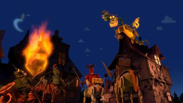 Die Feuerzangenbrüder schauen grinsend zu, wie es in der Stadt brennt. Daran sind sie schuld, weil sie einen angetäuschten Überfall zu ernst genommen und zu viel Feuer gespuckt haben. Ritter Rost wollte mit dieser Idee die Bedeutung der Ritter verdeutlichen - aber dieser Trick ging schief. | Rechte: ZDF/Caligari Film- und Fernsehproduktion
