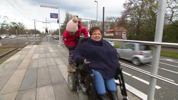 Manchmal darf Assol auch auf dem Rollstuhl ihrer Mutter mitfahren. | Rechte: Radio Bremen/Lür Wangenheim & Anna-Maria Meyer