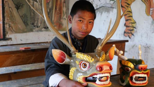 Yangka zeigt seine fertig gemalten Tiermasken. | Rechte: SWR/fechnerMEDIA GmbH