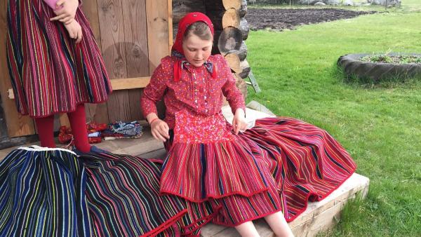 Anni erklärt die Farben der Röcke auf Kihnu: rot ist fröhlich, blau ist eher traurig. | Rechte: hr