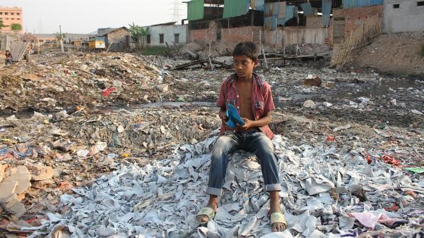 Ridoy sitzt inmitten riesiger Müllberge am Fluss hinter der Fabrik. | Rechte: SWR