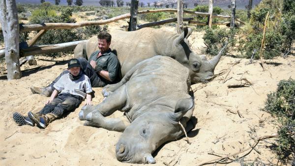 Satt und müde: Hunter und der Conservation Manager Divan machen eine Pause mit den beiden Nashornbabys Osita und Jambo  | Rechte: © HR / Wolfgang Müller