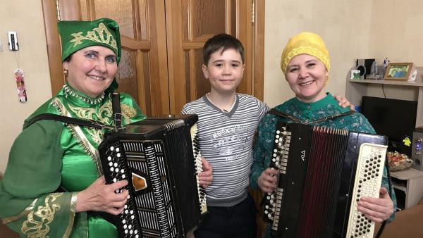 Azat steht zwischen seiner Mutter und seiner Tante. Beide tragen die typische Tracht der Tataren. | Rechte: KiKA