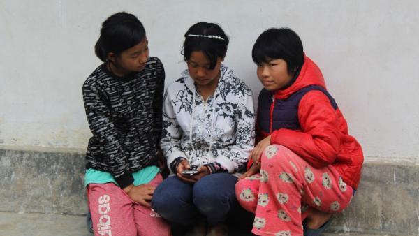 Tshering sieht sich mit Freundinnen Posts auf ihrem Handy an. | Rechte: SWR/Thinley Namgay
