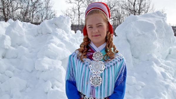 Mina wohnt mit ihren Brüdern und Eltern in Kautokeino, im hohen Norden Norwegens. Hier trägt sie die traditionelle Sami-Tracht. | Rechte: © RBB