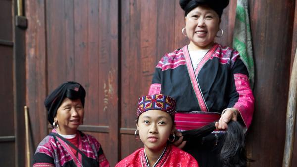 Panyuan mit ihrer Tante und ihrer Großmutter: Sie tragen die traditionelle Tracht und Frisur des Yao-Volkes. Die Frauen sind berühmt, weil sie die längsten Haare der Welt haben. | Rechte: SWR/Thomas Bresinsky