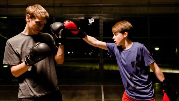 Während Jonny (Paul Hartmann, re.) versucht einen Deal mit Nils (Jacob Körner, li.) auszumachen, wird er heimlich von Raphael gefilmt. | Rechte: MDR/Marco Wicher