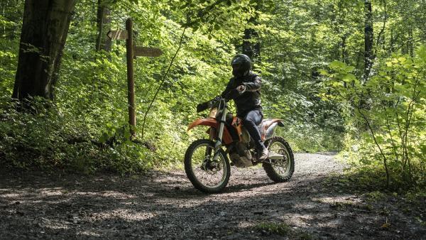 Ein Motorradfahrer braust durch den Wald und bemerkt nicht, wie er eine wichtige Spur verwischt. | Rechte: MDR/Saxonia Media/Felix Abraham