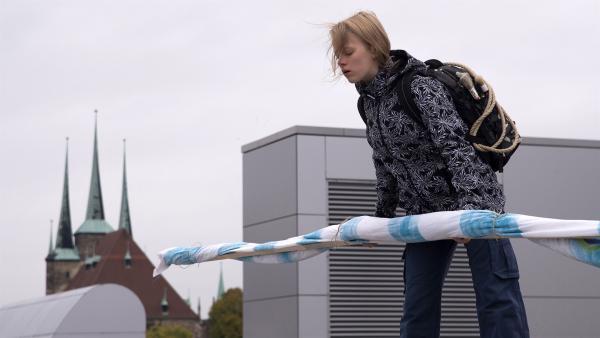 Martha (Luna Kuse) hat vor, ein großes Plakat von einem Dach hängen zu lassen. | Rechte: MDR/Saxonia Media/Katharina Simmet