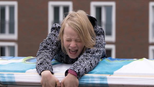 Beim Versuch, ein großes Plakat von einem Hausdach hängen zu lassen, gerät Martha (Luna Kuse) in große Gefahr. | Rechte: MDR/Saxonia Media/Katharina Simmet
