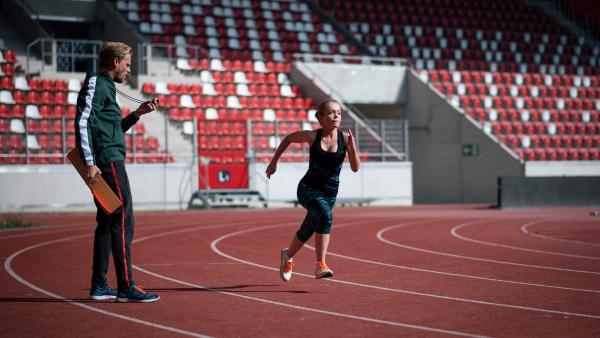 Sportkoordinator Hauser (Frederic Heidorn) prüft Cäcilias (Carlotta Weide) Lauftalent.   Rechte: MDR/Saxonia Media/Felix Abraham