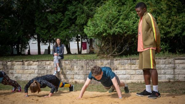 Badu (Arnold Makuissie, re.) gibt den harten Trainer. Anstrengend, finden Cäcilia (Carlotta Weide, li.) und Bela (Philip Müller, Mi.). | Rechte: mdr/Saxonia Media/Felix Abraham