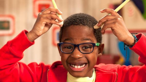 Amos hält sich zwei Stangen Zitronengras an den Kopf und lacht. | Rechte: René Rothkopf/ORF