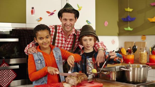 Heute wird gejodelt und geschunkelt, denn im Koch-Kids-Club gibt es Hausmannskost! Estelle, Elias und Profikoch Alex tischen einen deftigen Schweinebraten mit Kartoffelknödeln auf. | Rechte: ZDF/ORF/René Rothkopf