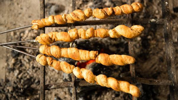 Passend dazu gibt es Stockbrot als Beilage, perfekt gebacken über dem offenen Feuer. | Rechte: ZDF/ORF/René Rothkopf