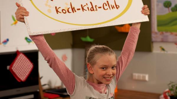 Theresa hält ein Schild des Koch-Kids-Club über ihrem Kopf | Rechte: René Rothkopf/ORF