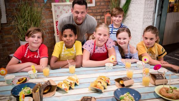 Alex Kumptner zeigt den Kochteams, was man aus Avocado so alles zaubern kann. Moderator und Fernsehkoch Alex Kumptner zusammen mit den Koch-Kids: Philip, Lukas, Anouk, Matthäus, Livia und Felicitas.   Rechte: ZDF//Rothkopf Rene