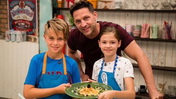 Fabian, Alex und Hannah präsentieren stolz gebackene Milchplätzchen in Kokosflocken mit Früchten. | Rechte: ZDF/Rothkopf Rene