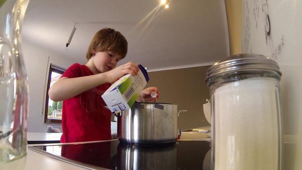 Nik schüttet Milch in einen Topf um Milchreis zu kochen. | Rechte: SWR