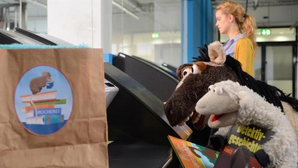 Wolle und Pferd sind völlig begeistert von der modernen Buchrückgabemaschine, müssen sich allerdings von Rieke (Friederike Linke) belehren lassen, dass pro Person maximal zehn Bücher ausgeliehen werden dürfen. | Rechte: NDR/Uwe Ernst