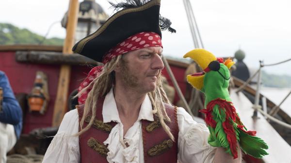 Hauptmann Schwarzsocke (Michael Kessler) streitet sich mit Polly.   Rechte: NDR/Sesame Workshop/Thorsten Jander