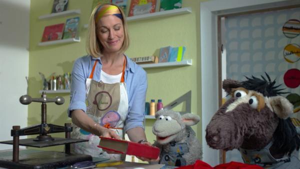 Julia hilft Wolle und Pferd dabei, das geliehene Buch zu reparieren. | Rechte: NDR/Sesame Workshop