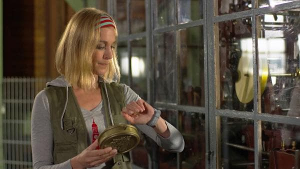 Julia erklärt ihnen, wie man die Uhr richtig stellt und abliest. | Rechte: NDR/Sesame Workshop