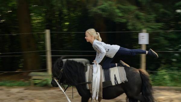 Die 7-jährige Hanna ist ein Sesamstraßen-Talent: sie liebt Ponys und turnt gern. Deswegen ist Voltigieren für sie das perfekte Hobby: Beim Voltigieren macht man nämlich Turnübungen auf einem Pferd. | Rechte: NDR/SesameWorkshop