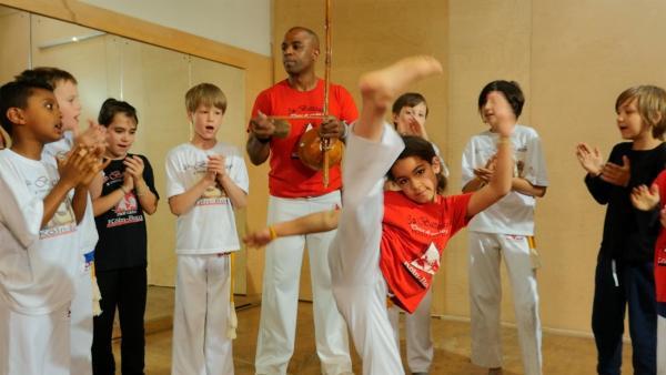 Die 7-jährige Tais hat ein Hobby, bei dem sie gleich drei Sachen können muss: turnen, kämpfen und Musik machen. Tais macht Capoeira. Das ist ein Kampftanz aus Brasilien. Damit tritt sie auf der Sesamstraßen-Bühne auf. | Rechte: NDR/SesameWorkshop