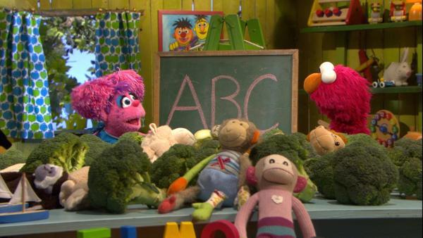 Abby, das pinke Monstermädchen steht links und Elmo, der rote Monsterjunge rechts vor einer Tafel auf der ABC steht. | Rechte: NDR