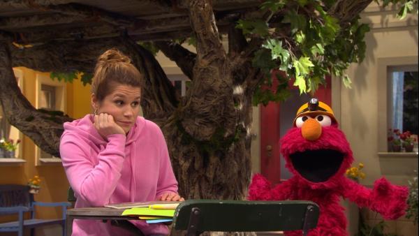 Christina im pinken Pullover und rechts das rote Monster Elmo mit Helm | Rechte: NDR Foto: Screenshot