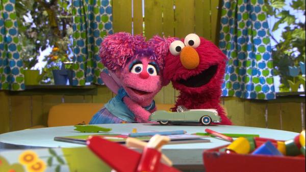 Das pinke Monster Mädchen Abby links umarmt den roten Monster Jungen Elmo rechts | Rechte: NDR