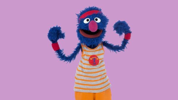 Das blaue Grobi Monster im Sport Outfit, mit rotem Stirnband, grau-orange gestreiftem Muskel-Shirt und roten Schweißbändern an den Handgelenken vor lila Hintergrund | Rechte: NDR