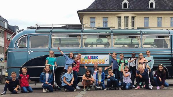 Auf der Fahrt im Musikexpress begegnet Singa vielen Kinderchören in Köln. | Rechte: ZDF/Firma MES GmbH